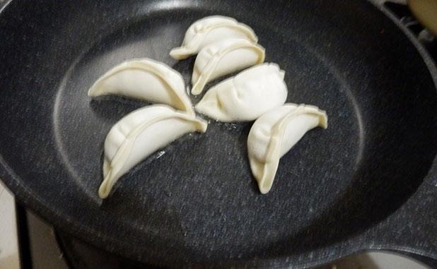 フライパンに少量の油をひき。冷凍餃子を並べる